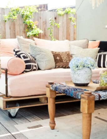 This pallet couch features armrests put together easily from inexpensive pipe found at your local home center.